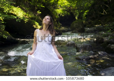 Happy young woman enjoying the pure waters of a mountain river in the forest