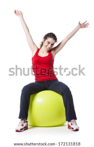 Happy young woman exercising with a yellow pilate ball (isolated on white) - stock photo
