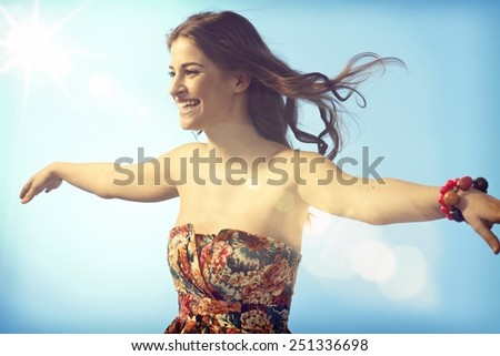 Happy young woman flying on summer sky, enjoying freedom arms wide open. - stock photo