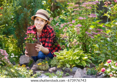 happy young woman gardener holding flower in pot people gardening care of flowers