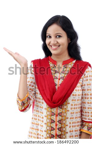 Happy young woman gesturing an open hand against white background - stock photo