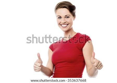 Happy young woman gesturing thumbs up to camera - stock photo