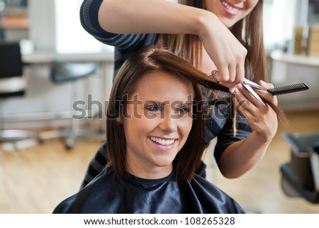 Happy young woman getting a new haircut by hairdresser at parlor - stock photo