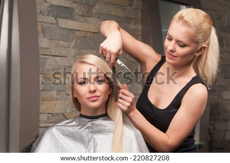 Happy young woman getting new haircut by hairdresser at parlor. blond hairdresser cutting client's hair in beauty salon - stock photo