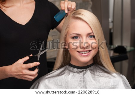 Happy young woman getting new haircut by hairdresser at parlor. hairdresser cutting client's hair in beauty salon - stock photo
