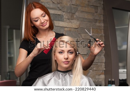 Happy young woman getting new haircut by hairdresser at parlor. redhead hairdresser cutting client's hair in beauty salon - stock photo