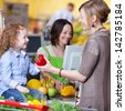 Happy young woman giving capsicum to daughter with cashier smiling in background at super market - stock photo