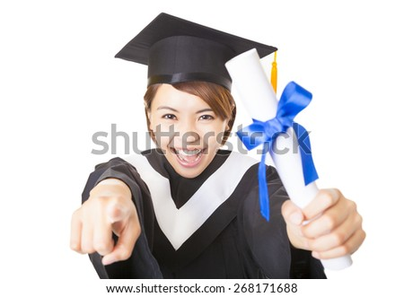happy young woman graduating and pointing to camera - stock photo