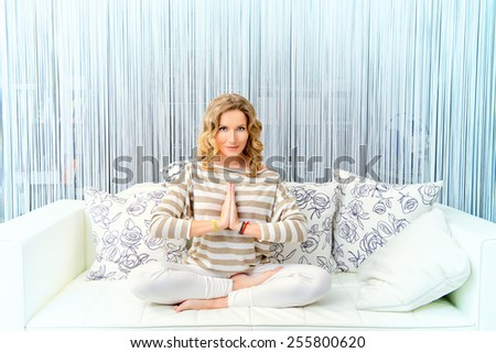 Happy young woman having a rest in her bedroom and doing yoga exercises. Home interior, furniture. Lifestyle. - stock photo