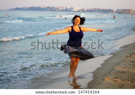 Happy young woman having fun at the beach