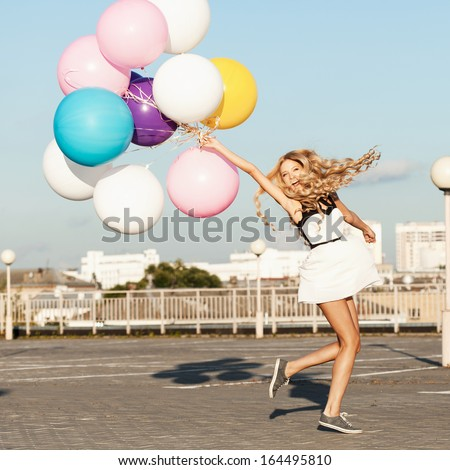 Happy young woman having fun with colorful latex balloons.  Gorgeous thick wavy hair. Outdoors, lifestyle - stock photo