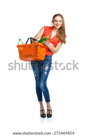 Happy young woman holding a basket full of healthy food on white background. Shopping