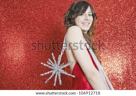 Happy young woman holding a Christmas star ornament over her shoulder against a red glitter background, smiling.