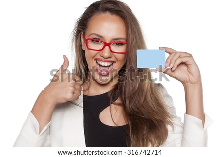 happy young woman holding a credit card and showing thumbs up - stock photo