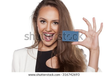 happy young woman holding a credit card on white background