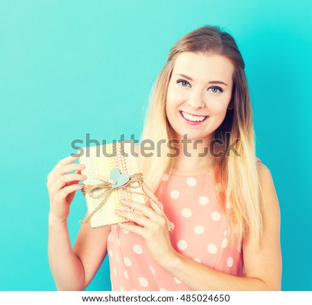 Happy young woman holding a gift box on a blue background