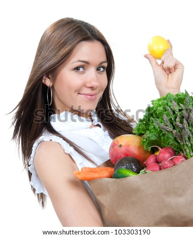 Happy young woman holding a paper shopping bag full of groceries, mango, salad, asparagus, radish, avocado, carrots and lemon in hand on white background - stock photo