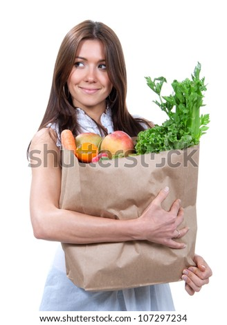 Happy young woman holding a paper shopping bag full of groceries, mango, salad, asparagus, radish, avocado  in hands on white background