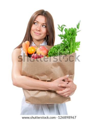 Happy young woman holding a paper shopping bag full of groceries, mango, salad, asparagus, radish, avocado, lemon, carrots on white background