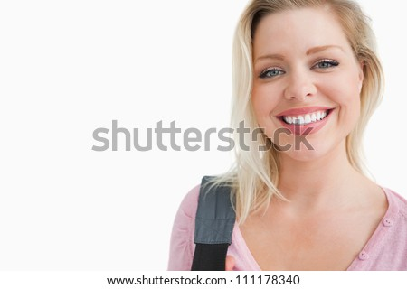 Happy young woman holding a shoulder bag against a white background
