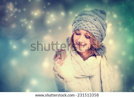 Happy young woman holding a small gift box - stock photo