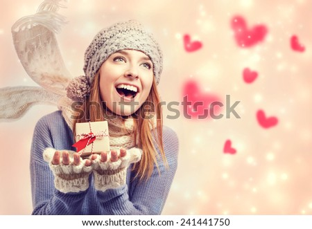 Happy young woman holding a small present box with red hearts - stock photo