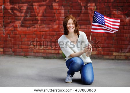 Happy young woman holding american flag. Independence Day concept. - stock photo