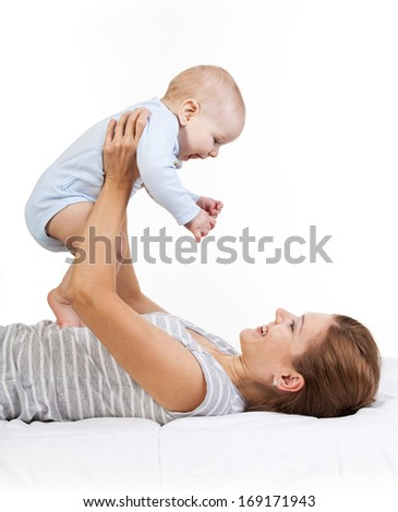 Happy young woman holding baby son while lying on back
