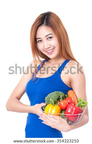 Happy young woman holding basket of vegetables. healthy concept