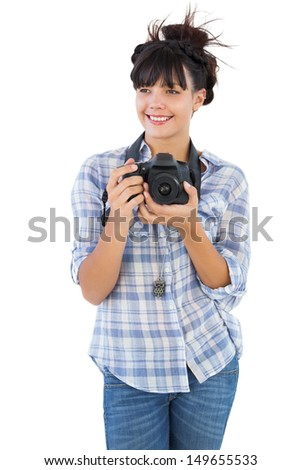 Happy young woman holding camera for taking picture on white background