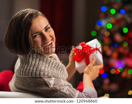 Happy young woman holding Christmas present box - stock photo