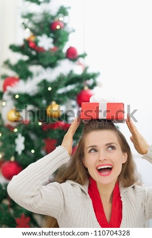 Happy young woman holding Christmas present box on head - stock photo