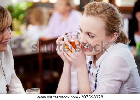 Happy young woman holding coffee cup while looking at female friend in cafe