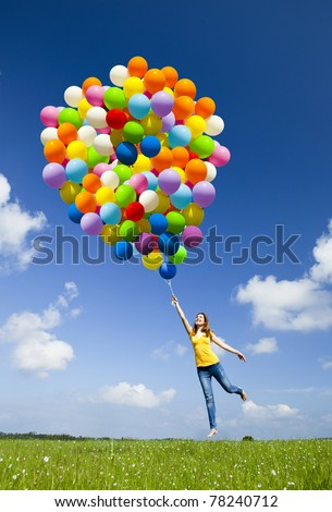 Happy young woman holding colorful balloons and flying over a green meadow - stock photo