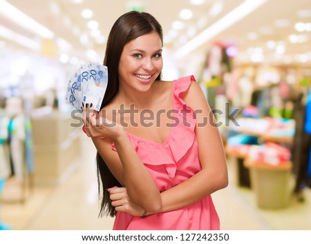 Happy Young Woman Holding Euro Currency at a mall - stock photo