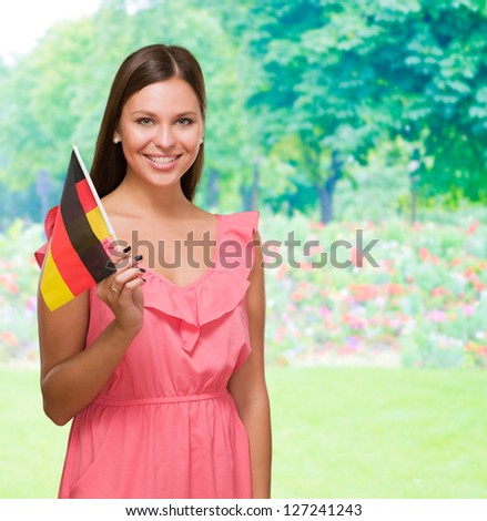 Happy Young Woman Holding German Flag against a nature background