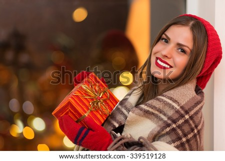 Happy young woman holding gift box - stock photo