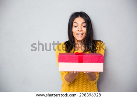 Happy young woman holding gift box over gray background - stock photo