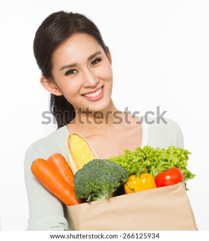 Happy young woman holding groceries bag  - stock photo
