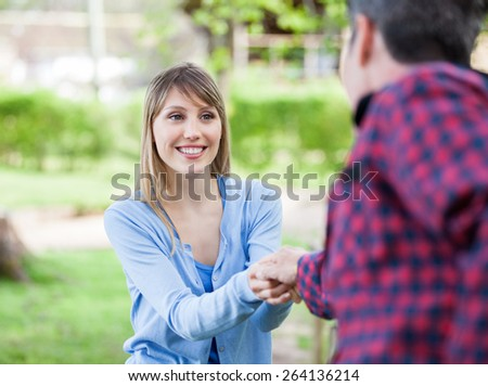 Happy young woman holding hand of boyfriend in park - stock photo