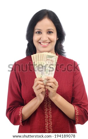 Happy young woman holding Indian currency notes against white background  - stock photo