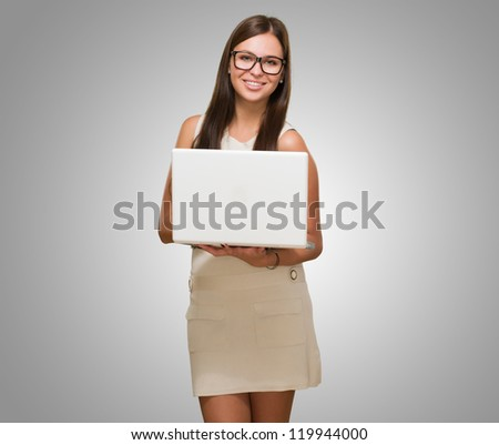 Happy Young Woman Holding Laptop against a grey background - stock photo