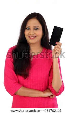 Happy young woman holding mobile phone against white background