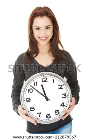 Happy young woman holding office clock