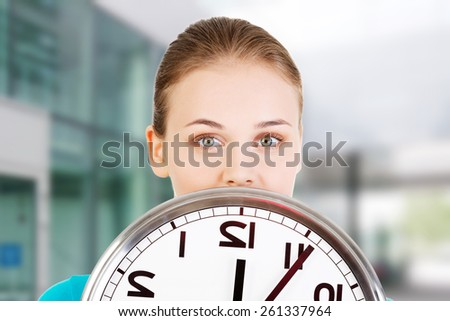 Happy young woman holding office clock. - stock photo