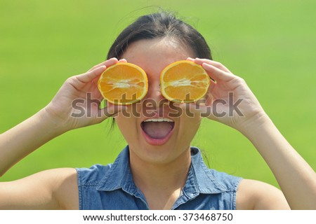 Happy young woman holding orange slices in front of eyes - stock photo