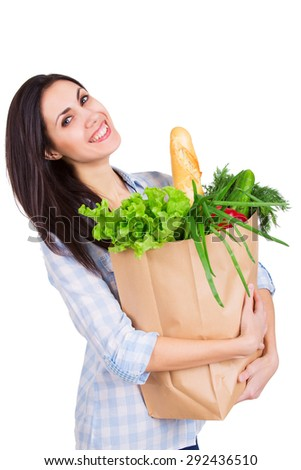 Happy young woman holding paper bag with groceries. Smiling girl customer. Consumerism. Isolated. - stock photo