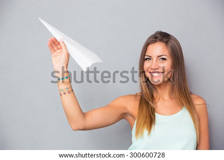 Happy young woman holding paper plane over gray background and looking at camera - stock photo