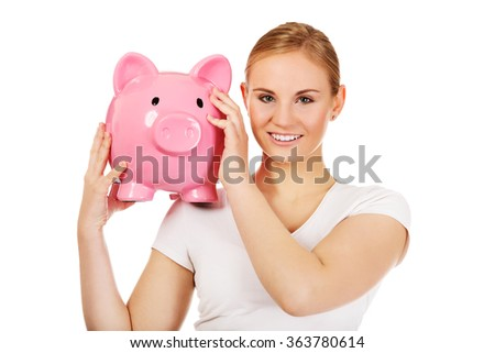 Happy young woman holding piggybank
