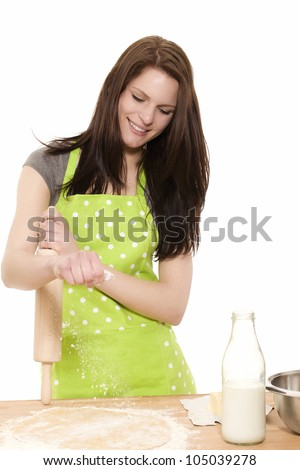 happy young woman holding rolling pin adding flour to dough on white background - stock photo